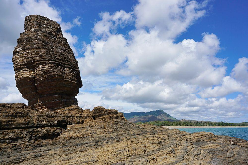 """遠浅の美しい海とビーチという""""ニューカレドニアらしい""""景観だけではなく、こんなワイルドな絵も撮れる、起伏に富んだ地形もブーライユの魅力です。写真は、かつては鍾乳洞だった岩が長い時間をかけて波に浸食されてできた奇岩「ラ・ロッシュ・ペルセ」。さらに海から内陸へと車を走らせると、小高い丘が連なり、その上からは息を飲むほど見事な青やグリーンのグラデーションの海を延々と見渡せます。"""